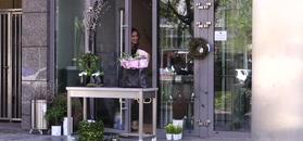 Maja Sablewska w kusych spodenkach grymasi w kwiaciarni
