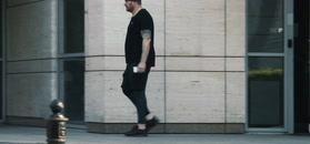 Tomasz Karolak w legginsach spaceruje z plikiem banknotów