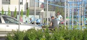 Skwaszony Tomasz Karolak na placu zabaw z dziećmi