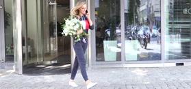 Karolina Pisarek z bukietem kwiatów opuszcza TVN